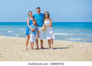 Happy family of four having fun at beach together. Fun happy lifestyle in the summer leisure