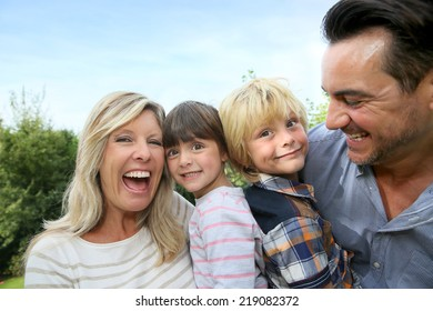 Happy family of four having fun outside