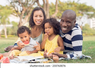 Happy family of four having picnic in the park