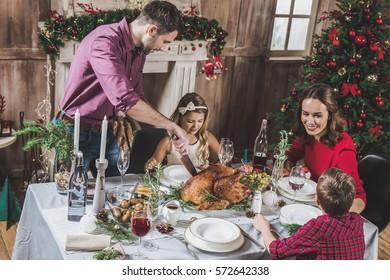 Happy family of four having roasted turkey for Christmas dinner