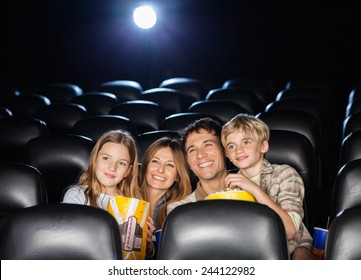 Happy family of four having snacks while watching film in movie theater