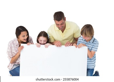 Happy family of four looking at billboard over white background