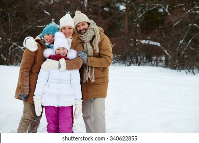 Happy family of four looking at camera in winter park
