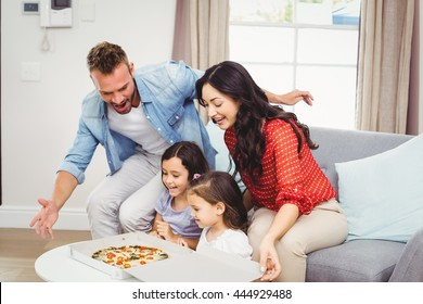 Happy family of four looking at pizza on table