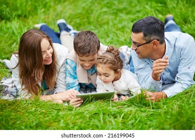 Happy family of four lying on grass with touchpad