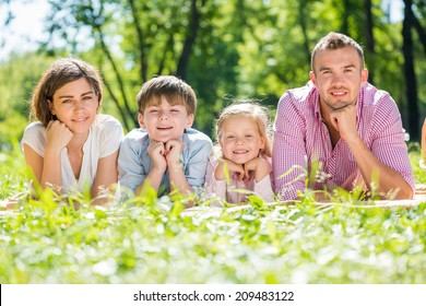 Happy family of four lying in summer park
