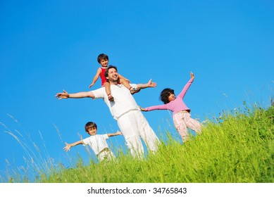 Happy family with four members on beautiful scene in nature