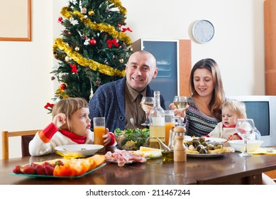Happy family of four over celebratory table at home interior