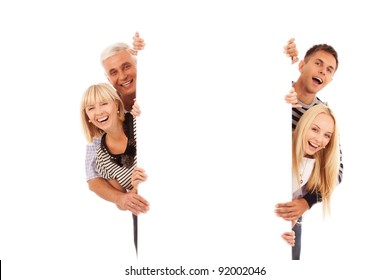 happy family of four peep out through the blank placard isolated on white