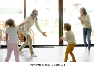 Happy family of four playing funny hide and seek game at home, blindfolded father trying to catch mother or children, parents and kids having fun laughing spending free time together in living room