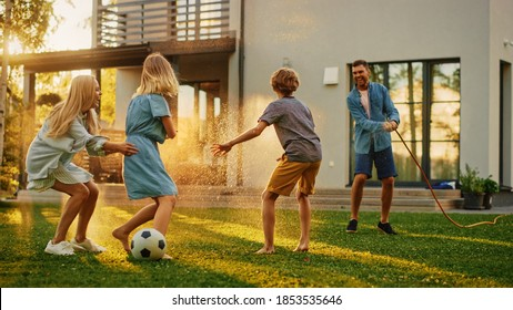 Happy Family of Four Playing with Garden Water Hose, Spraying Each Other. Mother, Father, Daughter and Son Have Fun Playing Games in the Backyard Lawn of Idyllic Suburban House on Sunny Summer Day