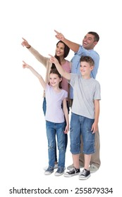 Happy family of four pointing at copy space over white background