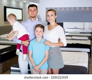 Happy family of four posing together in modern home furnishings store