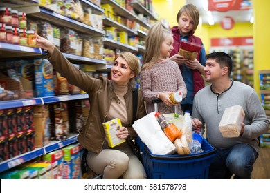 Happy family of four purchasing food in shop together