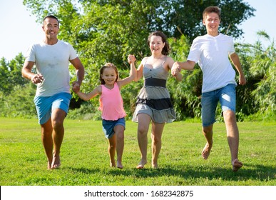 Happy family of four running on grass at summer park
