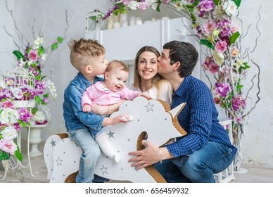 Happy family of four sit in room with flowers and play with little kids on her wooden toy horse. Closeup