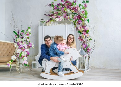Happy family of four sit in room with flowers and play with little kids on her wooden toy horse