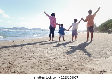 Happy family of four spend time and have fun together on summer holiday vacation, cheerful parents children hold and raise hand up from behind on tropical sea sand beach, resting and relaxing weekend.