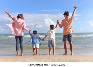 Happy family four spend time and have fun together on summer holiday vacation, cheerful parents children hold and raise hands up from behind on tropical sea sand beach, resting and relaxing weekend.