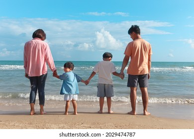 Happy family four spend time and have fun together on summer holiday vacation, cheerful parents children hold hands from behind on tropical sea beach, resting and relaxing weekend on beach.