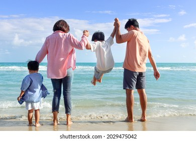 Happy family of four spend time together on summer holiday vacation, joyful parents kids hold hands from behind on tropical sea beach. Father, mother play with son, carry boy up, relaxation weekend.