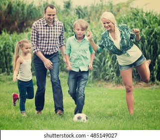 Happy family of four with teenager and little girl playing football on field. Focus on woman
