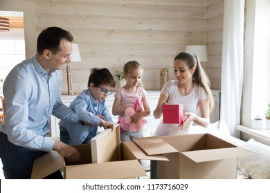 Happy family of four unpack cardboard boxes while moving to new house, mom dad and two small kids open carton packages with belongings, little children help parents with parcels while relocating