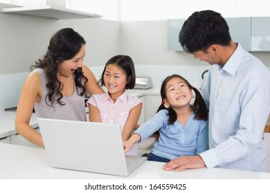 Happy family of four using laptop in the kitchen at home