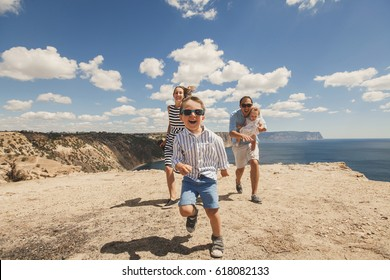 Happy family of four walking in the mountains. Family concept. Family trip.