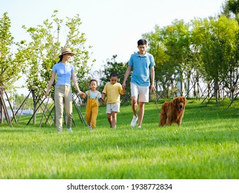 Happy family of four walking with the pet dog on the grass