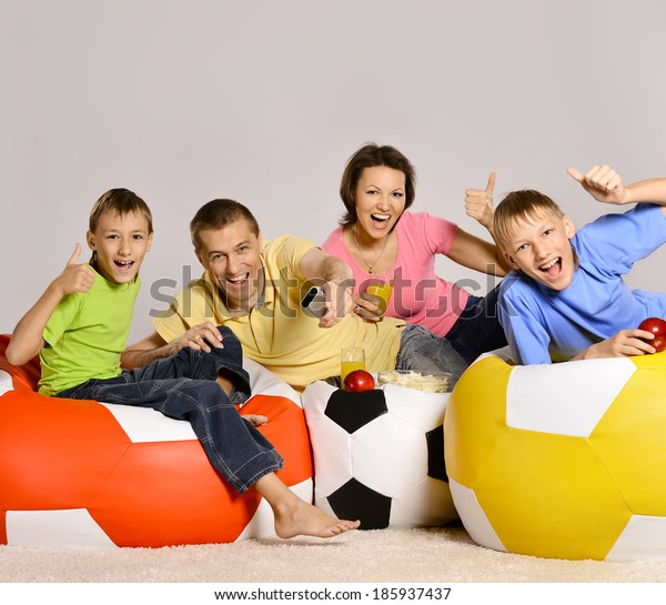 Happy family of four watching tv on colored cushions