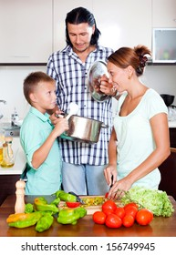 Happy family with fresh vegetables and greens in home kitchen
