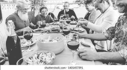 Happy family friends eating and drinking wine at barbecue dinner outdoor - Mature and young people having fun at bbq sunday meal - Food and summer lifestyle concept - Focus on hipster man face