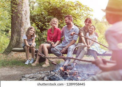 Happy family and friends roasting sausages over burning campfire at park