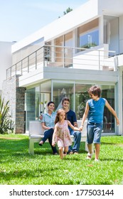 happy family in front of big modern new house outdoors, parents sitting on bench, children running on lawn grass smile