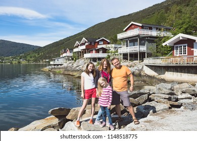 happy family -  fun smiling parents and their two daughters  near the traditional red Norwegian house, Norway