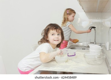 happy family funny kids in the kitchen, one girl cooking, her sisters washing dishes