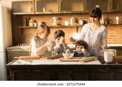 Happy family funny kids are preparing the dough, bake cookies in the kitchen. Three children and a mother  prepare food
