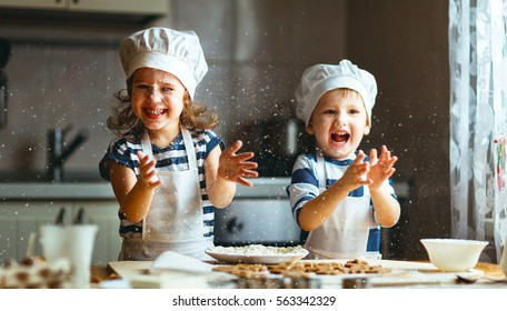 happy family  funny kids are preparing the dough, bake cookies in the kitchen
