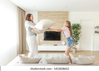 Happy family games. Single mother and her child girl are fighting pillows and jumping on couch