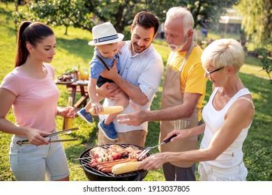 Fröhliche Familie versammelte sich um den Grill bei Picknick.Leisure, Food, Familie und Feiertage Konzept.
