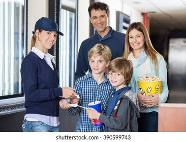 Happy Family Getting Tickets Checked By Worker At Cinema