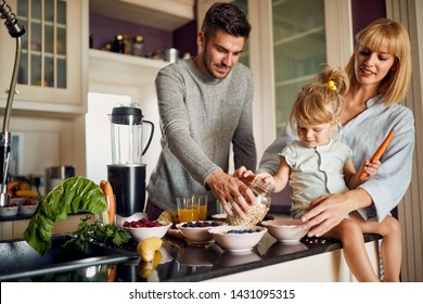 Happy family with girl in kitchen making breakfast together
