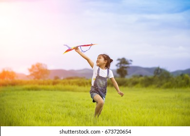 happy family .Girl runs kite in summer green pasture.