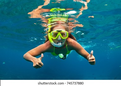 Happy family - girl in snorkeling mask dive with tropical fishes in coral reef sea pool. Travel lifestyle, water sports outdoor adventure, underwater swimming on summer beach holiday with kids.