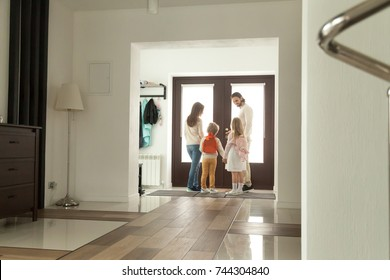 Happy family going out standing in hallway opening door, parents leaving home with kids holding son and daughter hands, mother father taking children to school, spending weekend together, rear view