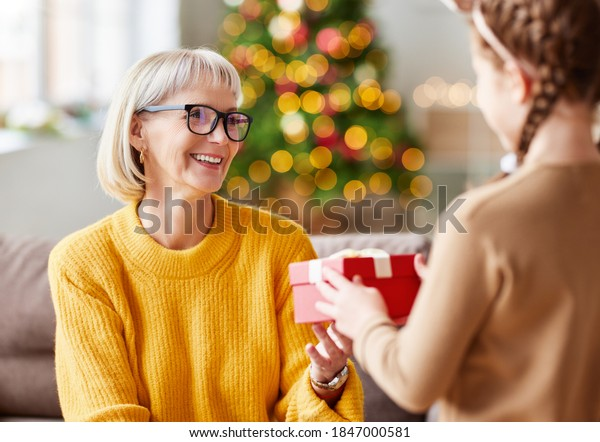 happy family granddaughter gives a cheerful smiling grandmother a Christmas gift at home