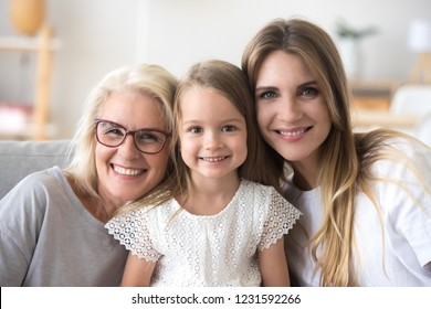 Happy family of grandmother, daughter and child girl looking at camera, smiling kid granddaughter posing with young mother and senior old mature grandma, three generations of women headshot portrait