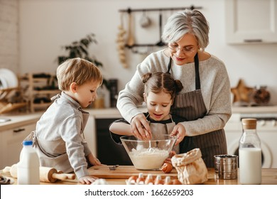happy family grandmother and grandchildren cook in the kitchen, knead dough and bake cookies