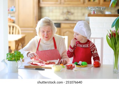 Happy family, grandmother with granddaughter, adorable little girl, preparing delicious pizza topping it with tomato sauce, vegetables and cheese, sitting at white dining table at bright sunny room